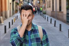 Terrified man covering his face outdoors.  royalty free stock image