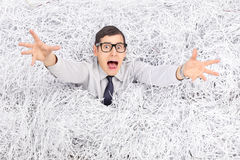 Terrified man drowning in a pile of shredded paper. Terrified young man drowning in a pile of shredded paper Royalty Free Stock Photo