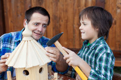 Terrified man holding nail while son handles the hammer Royalty Free Stock Photography