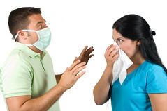 Terrified man with protective mask. Two people couple in a situation :woman sneeze in a white napkin while the man wearing a protective mask and it is very Stock Photo