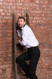 Terrified man trapped at the top of a ladder Royalty Free Stock Photography
