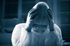 Terrified scientist in hazmat suit. Terrified scientist head in hands wearing hazmat protective suit Stock Image