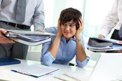 Terrified secretary. Touching her head while looking at big heaps of papers Royalty Free Stock Photo
