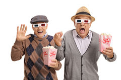 Terrified seniors with 3D glasses and popcorn Stock Photos