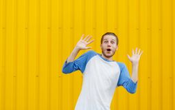 A scared young man with hands up on a wall background. Surprised man. Shock concept. Copy space. stock images