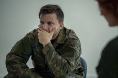 Terrified soldier in green uniform during meeting with psychotherapist. Terrified young soldier in green uniform during meeting with psychotherapist concept royalty free stock photos