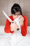 Terrified woman in bed with knife self defense Royalty Free Stock Photos
