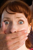 Terrified woman with covered mouth Stock Photo