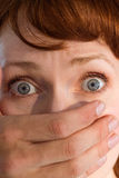 Terrified woman with covered mouth Royalty Free Stock Photo
