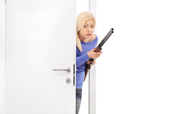 Terrified woman holding a rifle and entering a room stock photography