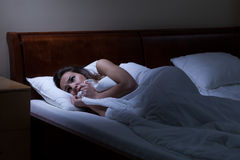 Terrified woman lying in bed Royalty Free Stock Photo