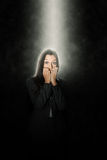 Terrified woman standing in a beam of white light. Shining down through the darkness from above looking at the camera with terror in her eyes and biting her Royalty Free Stock Image