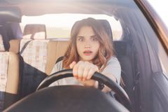 Terrified young cute female looks with depressed scared expression in front as drives car, has collision with other transport or a stock image