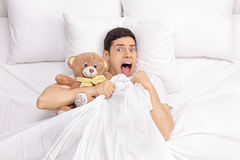 Terrified young man laying in bed Stock Photography