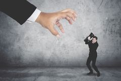 Terrifying businessman covering his face being attacked by a giant hand. Terrifying businessman in business suit covering his face being attacked by a giant hand Stock Photos