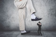 Terrifying businessman covering his face being attacked by a giant feet. Against grey wall Royalty Free Stock Photo