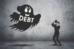 Terrifying businessman covering his face chased by a debt collector. Ghost Royalty Free Stock Image