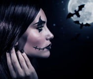 Terrifying witch in Halloween night. Side view of terrifying witch in Halloween night, bats on full moon background, portrait of werewolf on scary dark night Royalty Free Stock Photos