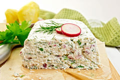 Terrine of curd and radish on paper and board. Terrine of curd and radish with dill, green onions on a paper and a board, knife, bread, boiled potatoes, napkin Royalty Free Stock Photography