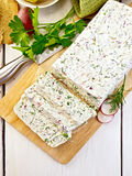 Terrine of curd and radish on paper and board top. Terrine of curd and radish with dill, green onions on a paper and a board, knife, bread, napkin, parsley on a Royalty Free Stock Images