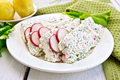 Terrine of curd and radish in plate on light board. Sliced curd terrine with dill and radishes, green onions, salad on a plate, boiled potatoes, napkin, parsley Royalty Free Stock Photos