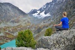 Territoire d'Altai, secteur d'Ust-Koksinsky, Russie, septembre, 06, 2016 La jeune femme médite sur une falaise au-dessus du lac K Photographie stock