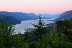 Territorial Evening Glow. Beautiful evening glow over the Columbia River Gorge. Green trees in forefront, Vista House on the cliff, Beacon Rock in the distance Stock Photography