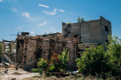 The territory of the abandoned factory, old abandoned buildings, metal structures Stock Photos