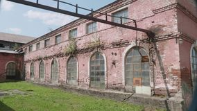 Territory of abandoned metallurgical plant with building of warehouse built with red brick. stock video