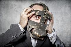Terror, hombre de negocios con la máscara del hierro Foto de archivo