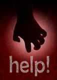 Terrorific help. A hand appears from the black while it reads a help message Stock Photography