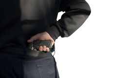Terrorism. Problems of terrorism and the unauthorized application of shooting iron. Person holds(hide) a handgun behind a back. Shadow on a back Royalty Free Stock Photos