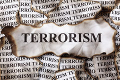 Terrorism. Burnt Terrorism. Burnt pieces of paper with the word Terrorism. Close-up Royalty Free Stock Images