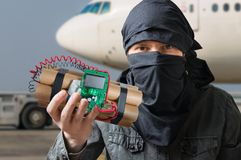 Terrorism concept. Terrorist in airport holds dynamite bomb in hand Royalty Free Stock Photography