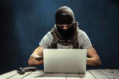 Terrorism concept. Terrorist working on his computer. Terrorism concept Royalty Free Stock Photo