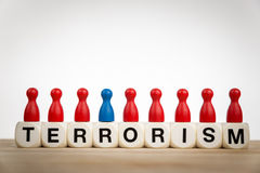 Terrorism concept with toy dice and differently colored pawn Royalty Free Stock Photo