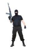 Terrorist. Portrait of dangerous bandit in black wearing balaclava and holding gun in hand Royalty Free Stock Image