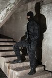 Terrorist in black mask on staircase. Man in black uniform holding M-16 rifle standing on stairs Royalty Free Stock Photography