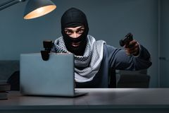 The terrorist burglar with gun working at computer. Terrorist burglar with gun working at computer royalty free stock image