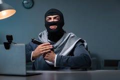 The terrorist burglar with gun working at computer. Terrorist burglar with gun working at computer stock photo