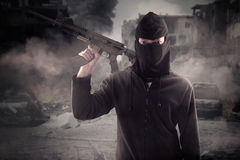 Terrorist carrying rifle at broken city Royalty Free Stock Images