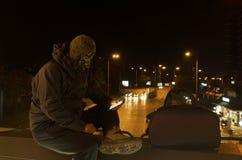 Terrorist in der Mitte einer Stadt, die auf einer Brücke sitzt lizenzfreies stockbild