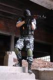 Terrorist in der schwarzen Schablone, die mit einer Gewehr zielt stockbilder
