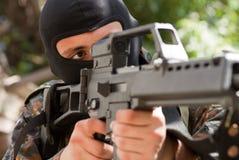 Terrorist in der schwarzen Schablone mit einer Gewehr stockbild