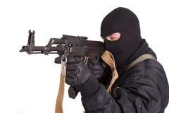Terrorist in der schwarzen Uniform und Maske mit der Kalaschnikow lokalisiert lizenzfreie stockbilder