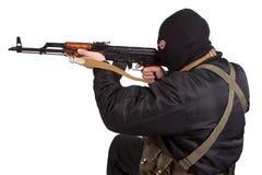 Terrorist in der schwarzen Uniform und Maske mit Kalaschnikow stockbild