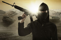 Terrorist with gun and military vehicle. Male terrorist wearing mask and holding a machine gun with military vehicle background royalty free stock images