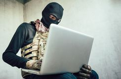 Terrorist is hacking. Terrorist is using a computer to perform a security drill fighter from an abandoned house royalty free stock photography