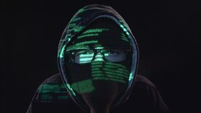 Terrorist copies information from the computer. Black background. Close up. Terrorist looks at the computer and copies information from the computer to an stock footage