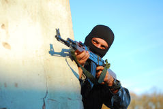 Terrorist with mask and gun. Terrorist with mask hidden behind a wall and aiming with his gun stock photos
